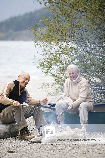 Germany  Bavaria  Walchensee  Senior couple sitting at campfire  grilling fish