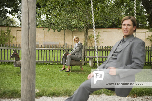 Germany  business people sitting in playground
