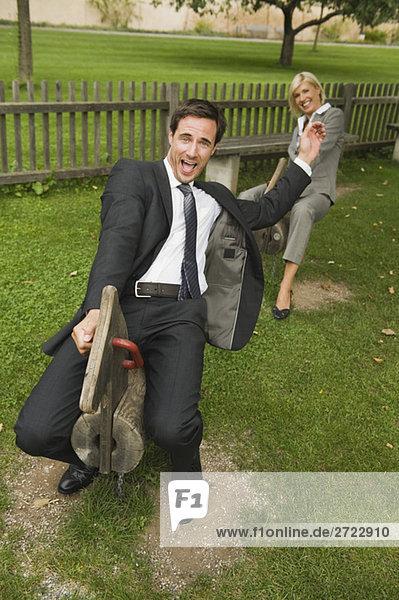 Deutschland  Geschäftsleute auf Schaukelpferden auf dem Spielplatz Deutschland, Geschäftsleute auf Schaukelpferden auf dem Spielplatz