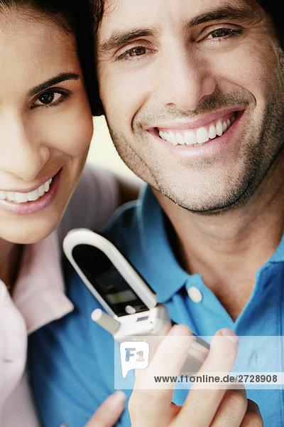 Porträt eines jungen Mannes hält ein Mobiltelefon und lächelnd mit einer jungen Frau