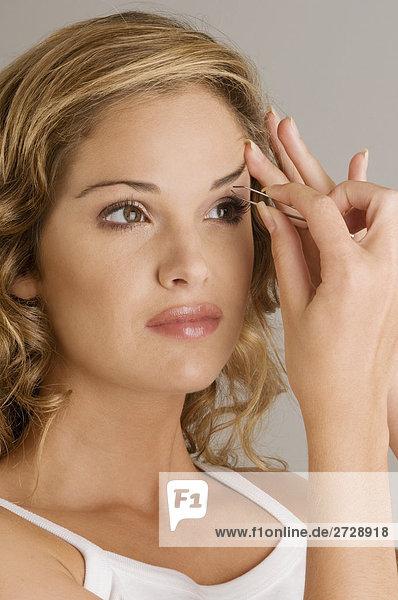 Nahaufnahme einer jungen Frau ihre Augenbrauen zupfen