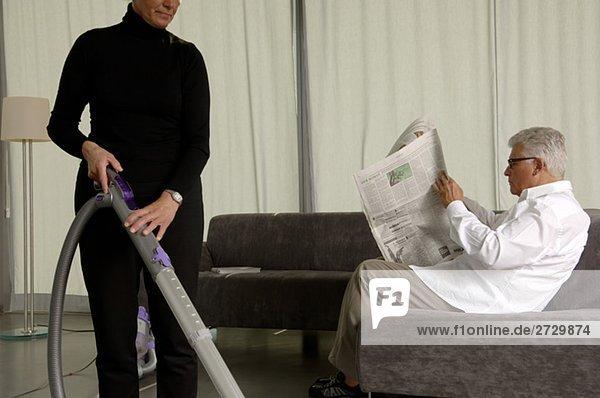 Frau arbeitet mit Staubsauger  während ihr Ehemann lesend auf einer Couch sitzt  fully_released