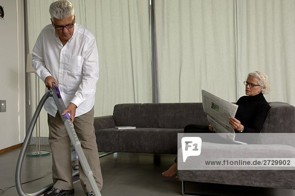 Älterer Mann beim Staubsaugen während seine Frau daneben sitzt und eine Zeitung liest  fully_released