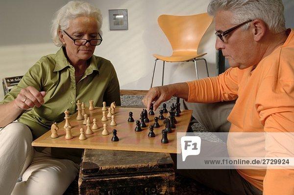 Älterer Mann und ältere Frau spielen gemeinsam Schach  fully_released