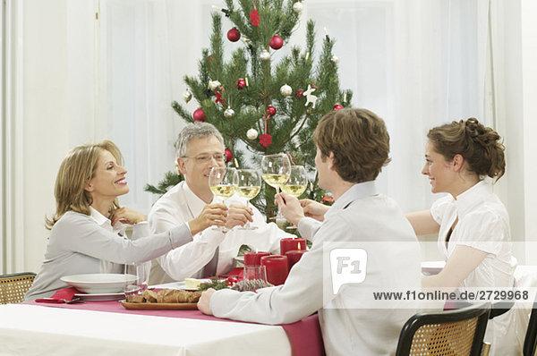 Vier Personen sitzen an einem Tisch und stoßen mit Weißwein an