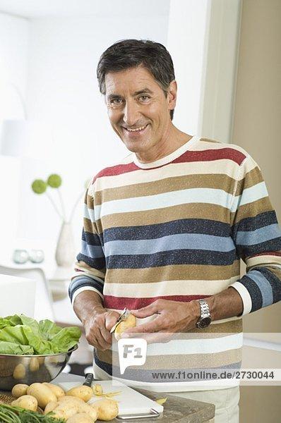 Älterer Mann schält Kartoffeln  fully_released