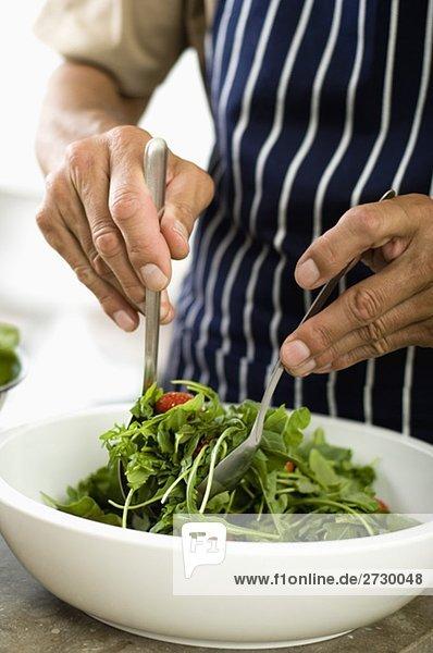 Älterer Mann bereitet Salat zu  fully_released