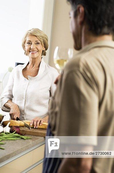 Alte Frau schneidet Baguette  Mann trinkt ein Glas Weißwein  fully_released
