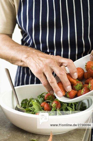 Älterer Mann bereitet Salat mit Erdbeeren zu  fully_released