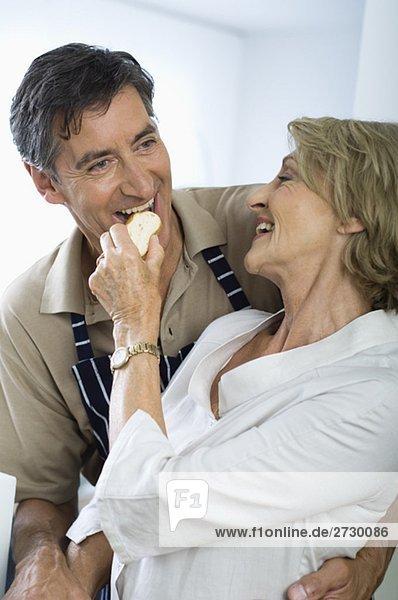 Frau füttert Mann mit einem Stück Baguette  fully_released