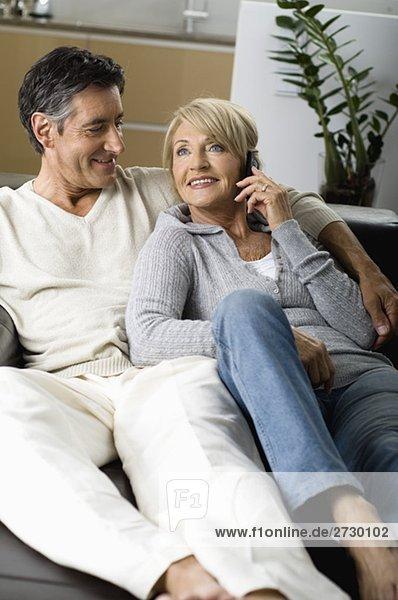 Paar sitzt auf einem Sofa und telefoniert  fully_released