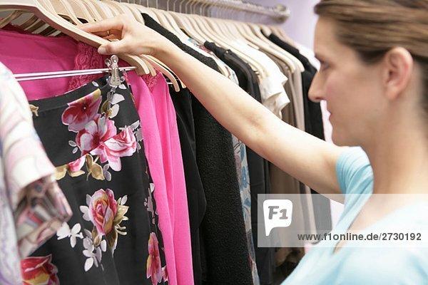 Schwangere Frau beim Shopping  wählt Kleidung aus  fully_released