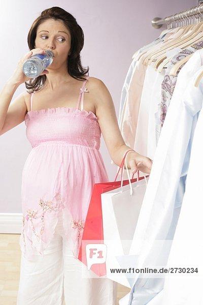 Schwangere Frau beim Shopping  trinkt Wasser  sieht sich Kleider an  fully_released