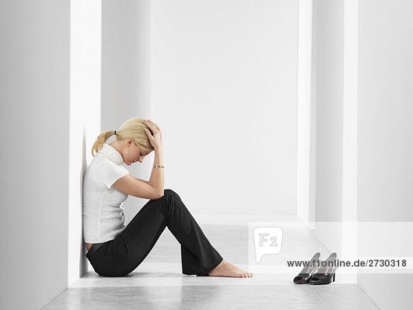 Frau sitzt niedergeschlagen in einem Gang