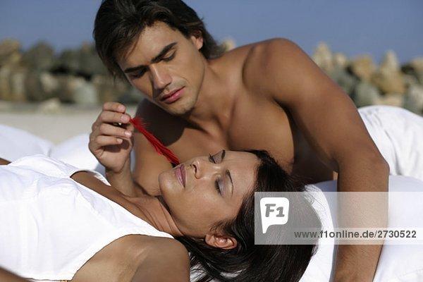 Mann streichelt Frau mit einer roten Feder  fully_released