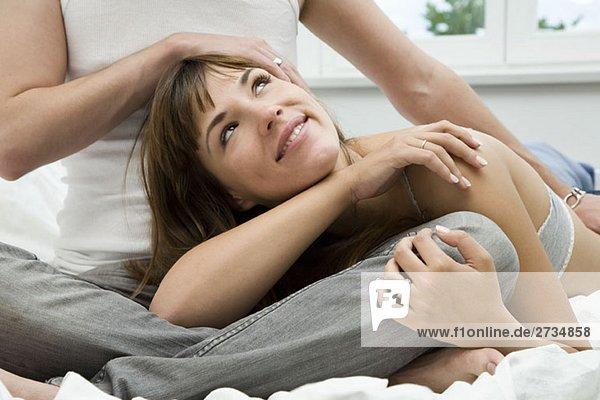Ein Paar  das sich auf einem Bett umarmt.