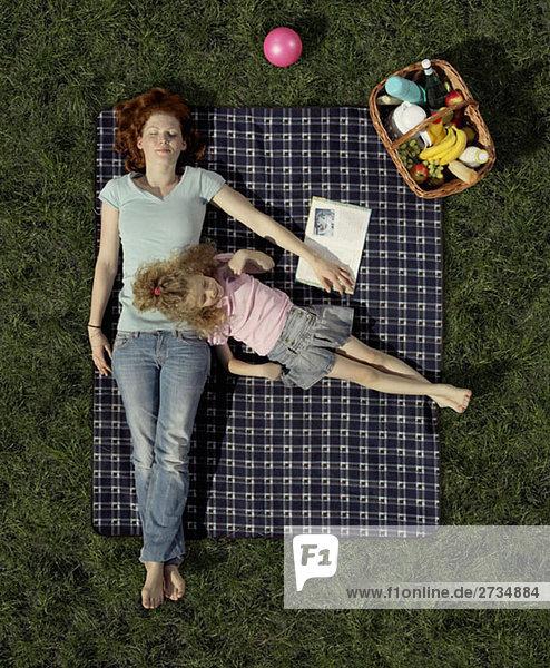 Eine Mutter und eine Tochter  die auf einer Decke auf dem Gras liegen und sich ausruhen.