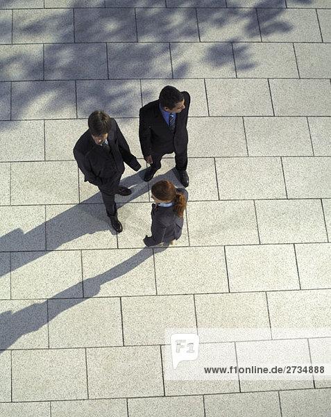 Drei Geschäftsleute stehen zusammen