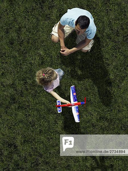 Ein Vater  eine Tochter  die mit einem Spielzeugflugzeug spielt.