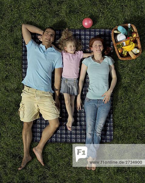 Eine Familie  die auf einer Decke im Gras liegt.