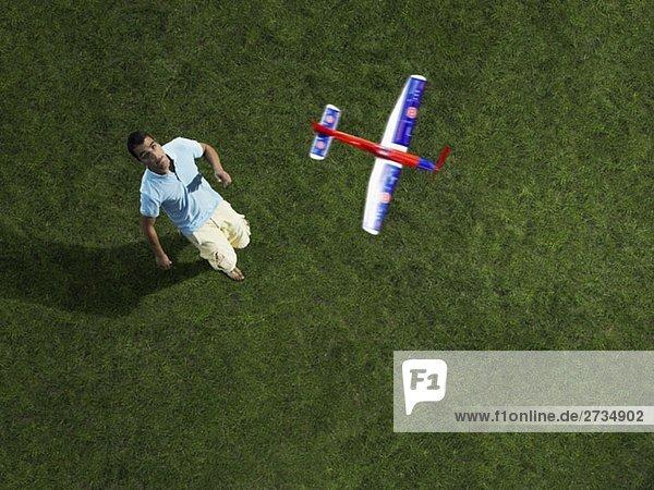 Ein Mann schaut auf ein Spielzeugflugzeug  das in der Luft fliegt.