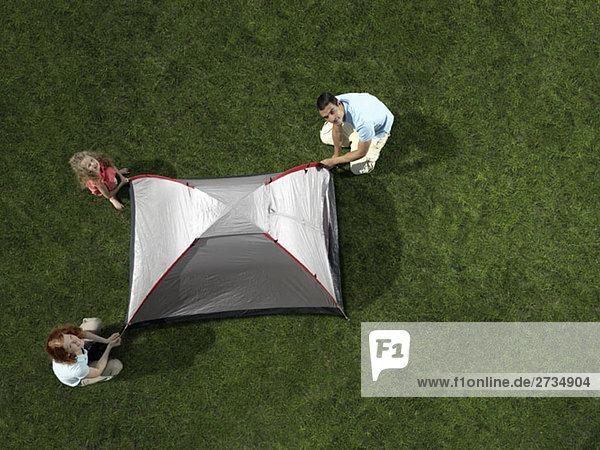 Eine Familie baut ein Zelt auf Rasen auf.
