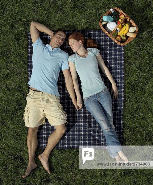 Ein junges Paar schläft auf einer Decke im Park.