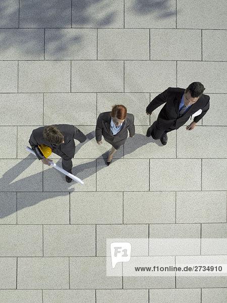 Drei Geschäftsleute mit Schutzhelm und Bauplan