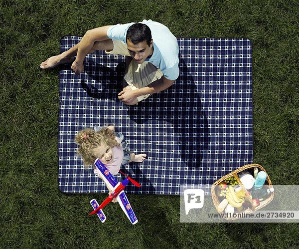 Vater und Tochter beim Picknick und Spielen mit einem Spielzeugflugzeug