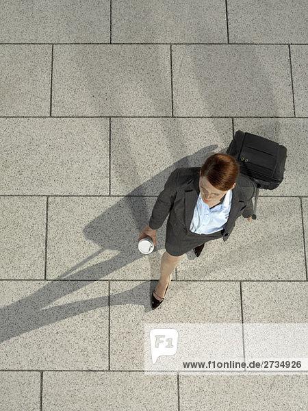 Eine Geschäftsfrau  die einen Koffer zieht und einen Kaffee hält.