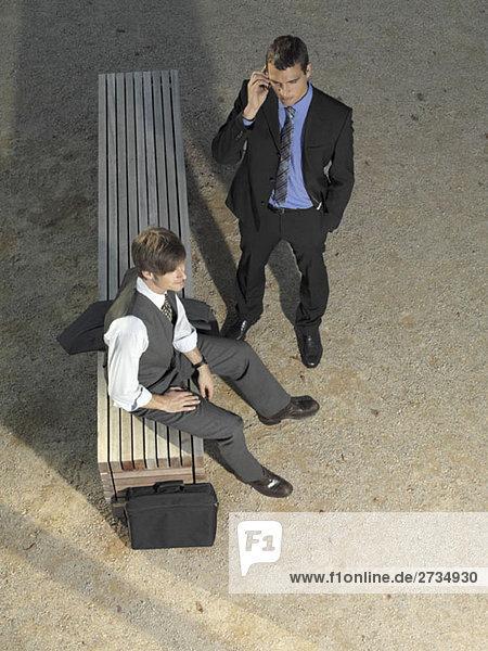 Zwei Geschäftsleute warten an einer Bank.