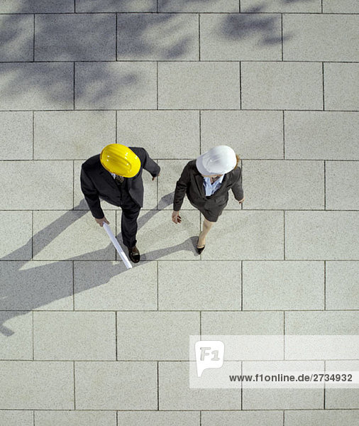 Zwei Geschäftsleute mit Schutzhelmen