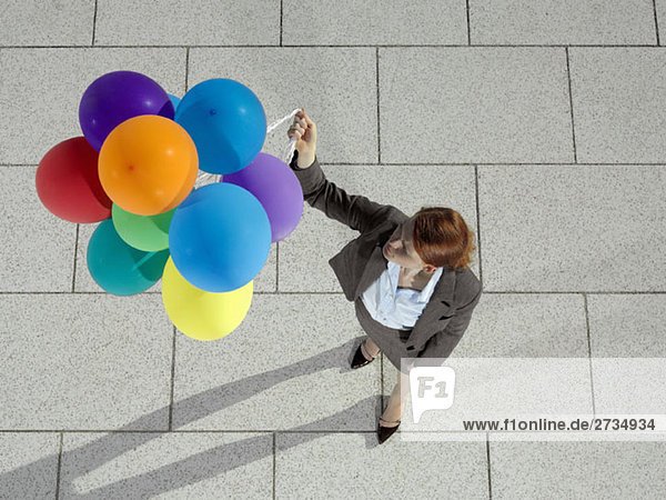 Eine Geschäftsfrau  die einen Haufen Heliumballons hält.
