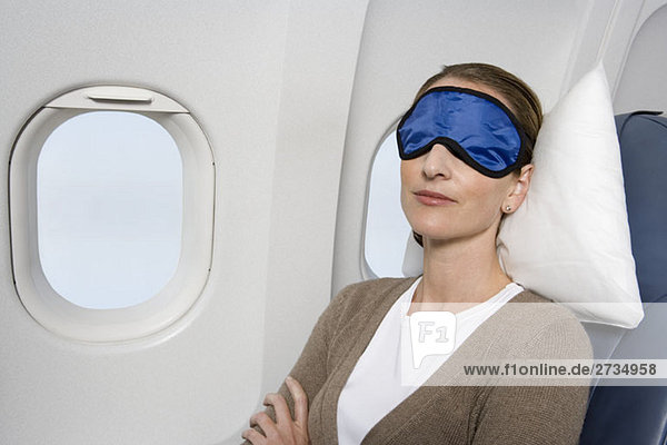Eine Frau mit Schlafmaske,  die im Flugzeug schläft.