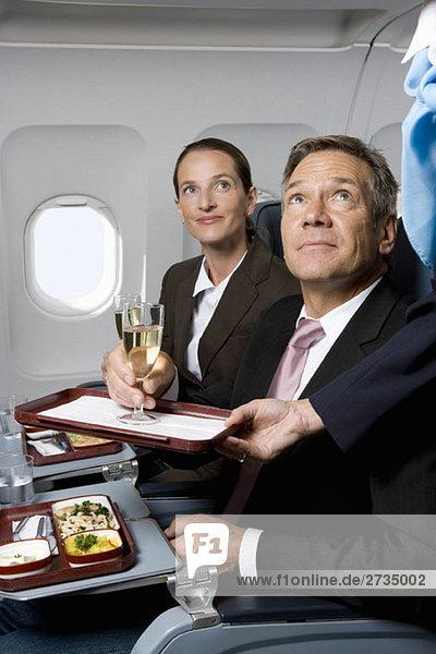 Geschäftsleute in einem Flugzeug  die Mahlzeiten und Champagner bekommen.