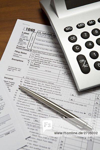 Taschenrechner und Stift auf einem Steuererklärungsformular