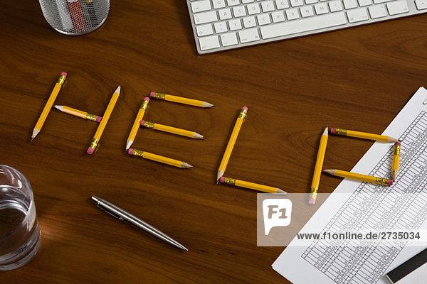 Bleistifte auf einem Schreibtisch  die so angeordnet sind  dass sie Hilfe buchstabieren.