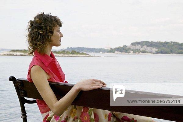 Eine Frau  die auf einer Bank sitzt und auf das Meer schaut.