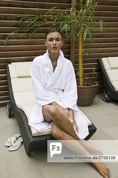 Eine Frau im Bademantel sitzt am Rand eines Sessels