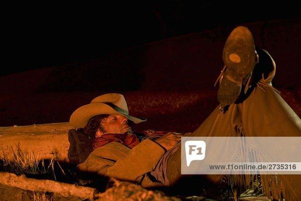 Ein Cowboy schläft am Lagerfeuer Ein Cowboy schläft am Lagerfeuer