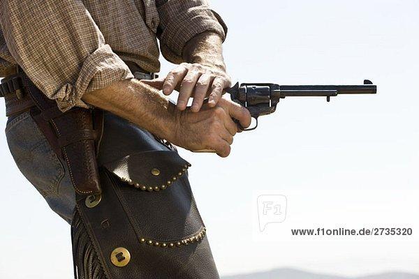 Seitenansicht eines Cowboys mit einer Waffe Seitenansicht eines Cowboys mit einer Waffe