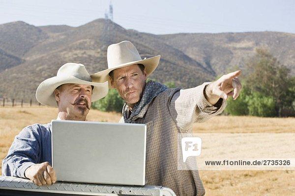 Zwei Cowboys  die einen Laptop benutzen und darauf zeigen. Zwei Cowboys, die einen Laptop benutzen und darauf zeigen.