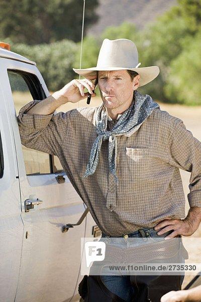 Ein Cowboy lehnt sich an sein Auto und redet in seinem Handy Ein Cowboy lehnt sich an sein Auto und redet in seinem Handy