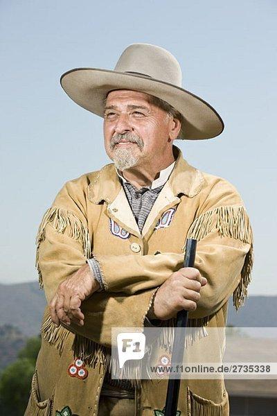 Porträt eines Cowboys  der mit seiner Waffe steht Porträt eines Cowboys, der mit seiner Waffe steht