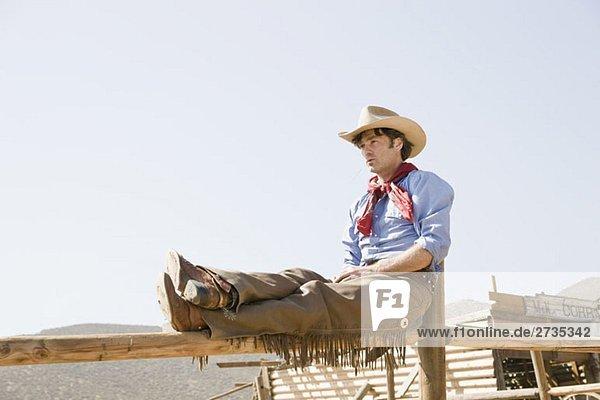 Ein Cowboy sitzt auf einem Zaun und entspannt sich. Ein Cowboy sitzt auf einem Zaun und entspannt sich.