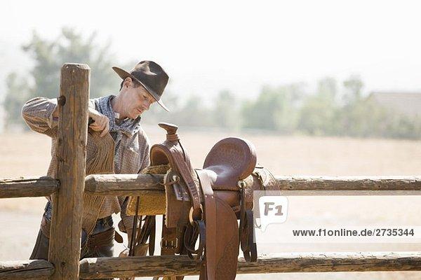 Ein Rancher  der einen Pferdesattel auf einem Zaun vorbereitet. Ein Rancher, der einen Pferdesattel auf einem Zaun vorbereitet.