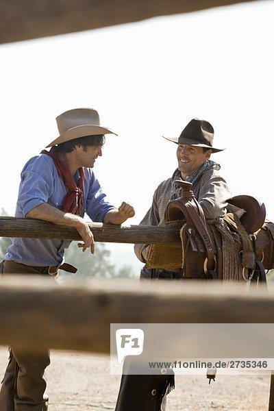 Zwei Rancher  die neben einem Zaun reden. Zwei Rancher, die neben einem Zaun reden.