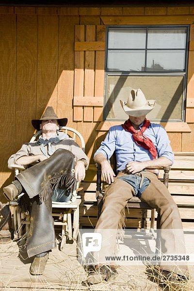 Zwei Cowboys schlafen in Stühlen. Zwei Cowboys schlafen in Stühlen.