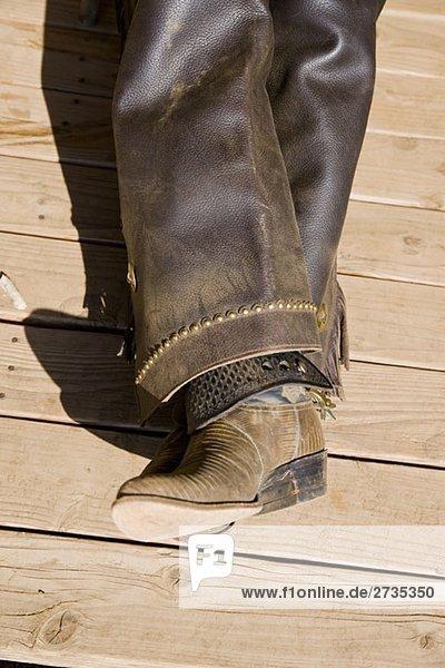 Lederstiefel und Chaps eines auf einem Holzboden liegenden Cowboys Lederstiefel und Chaps eines auf einem Holzboden liegenden Cowboys