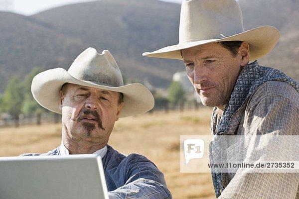 Zwei Cowboys schauen zusammen auf einen Laptop Zwei Cowboys schauen zusammen auf einen Laptop